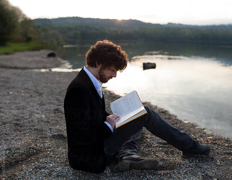 Young handsome bearded man reading a book sitting by a lake during sunset. by Luca Di Lotti for Stocksy United