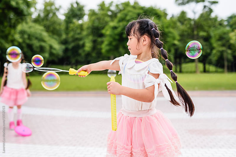 Side view of black-haired girl playing with soap bubbles in park by Lawren Lu for Stocksy United