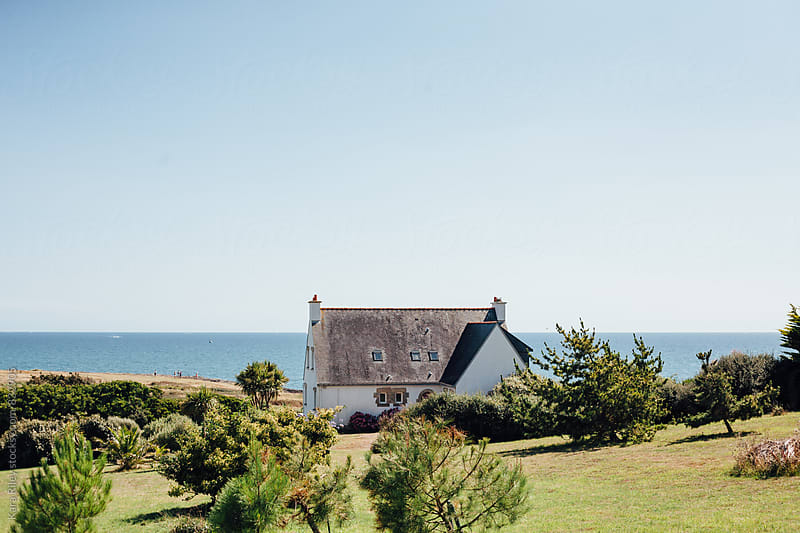 House on a hill near the ocean by Kara Riley for Stocksy United