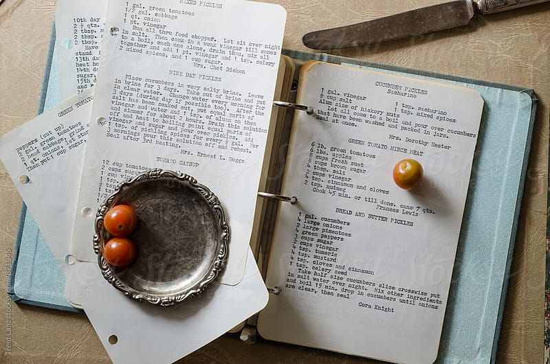 Recipe book and cherry tomatoes on silver plate by Trent Lanz for Stocksy United