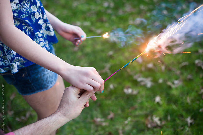 Father handing his daughter a sparkler by Carolyn Lagattuta for Stocksy United