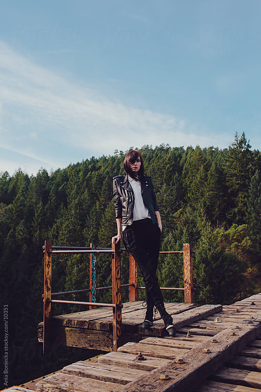 A woman standing on a ledge by Ania Boniecka for Stocksy United