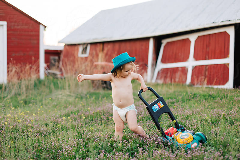 Small child playing with lawn mower by Jessica Byrum for Stocksy United