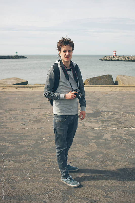 Young guy is standing on a jetty with his camera by Koen Meershoek for Stocksy United