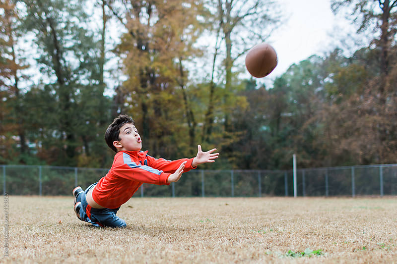 Young boy playing football on a practice field by Jakob for Stocksy United