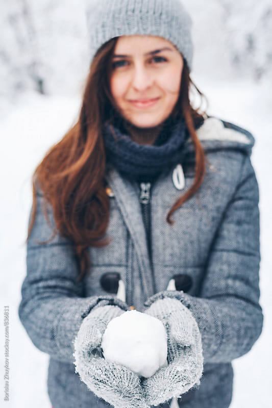 Woman holding snowball by Borislav Zhuykov for Stocksy United