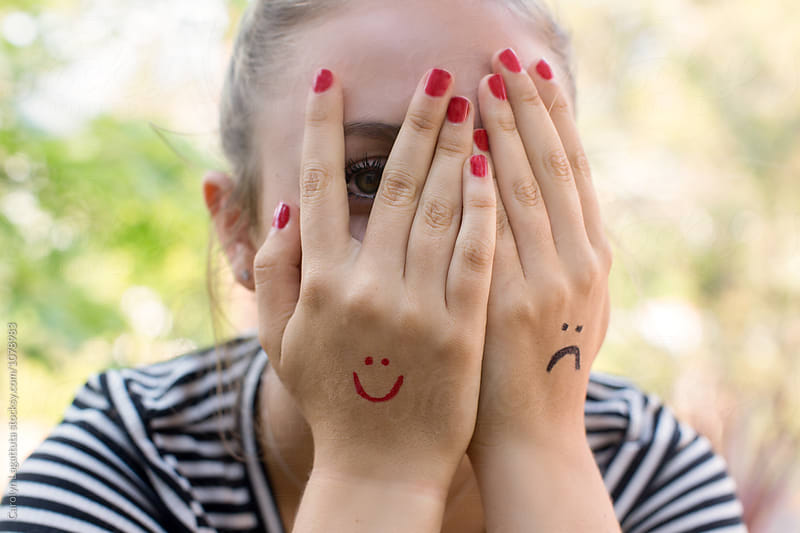 Teenage girl with a smiley and a frown drawn on her hands by Carolyn Lagattuta for Stocksy United