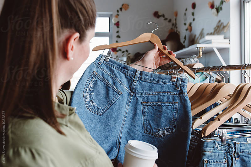 Young woman shopping for denim shorts in clothing store by Carey Shaw for Stocksy United