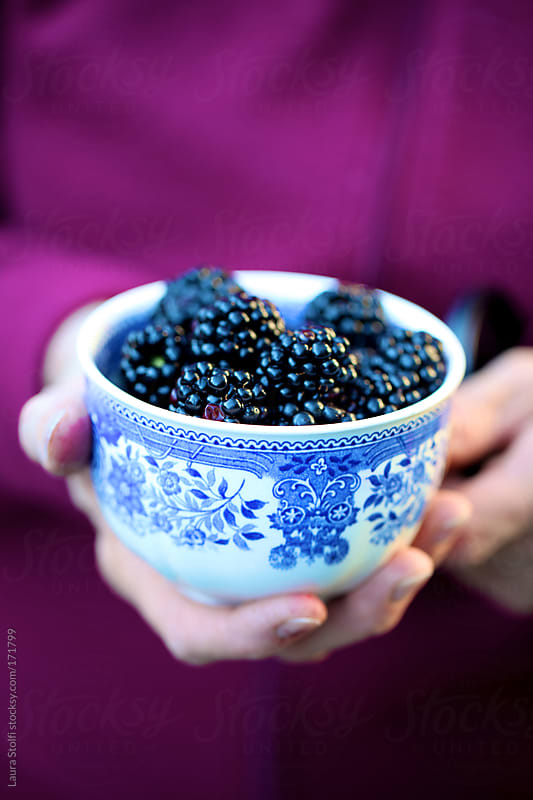 Woman with vintage china cup filled with fresh blackberries by Laura Stolfi for Stocksy United