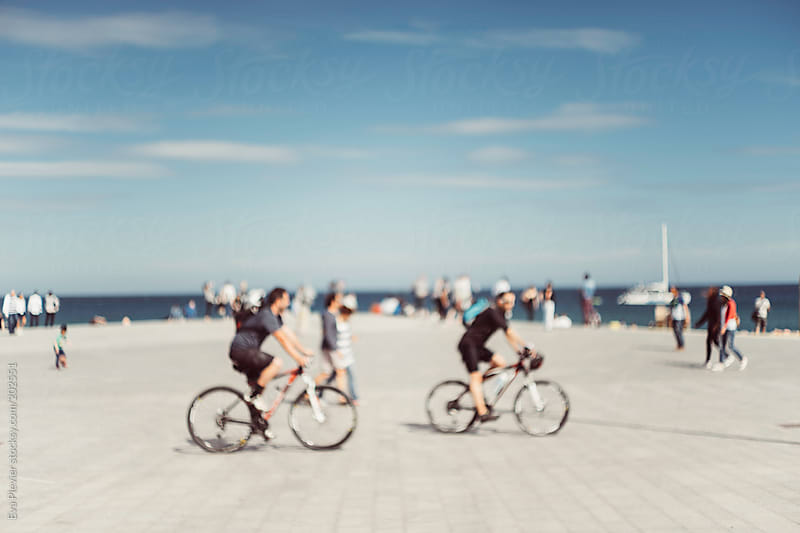 People on a bicycle riding by the shore.  by Eva Plevier for Stocksy United
