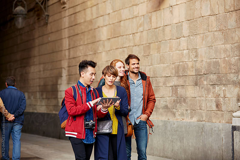 Couple Using Digital Tablet While Walking With Friends by ALTO IMAGES for Stocksy United