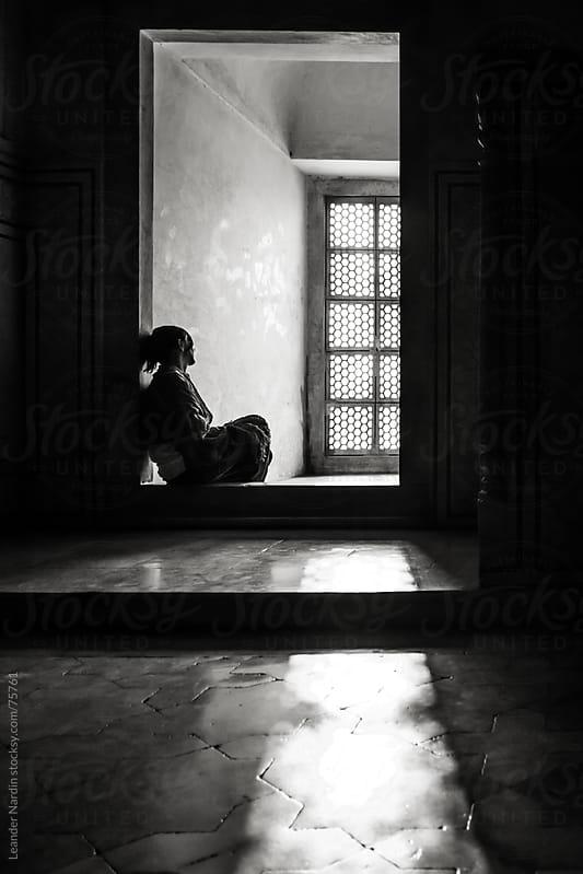 woman sitting in front of a window inside the taj mahal by Leander Nardin for Stocksy United