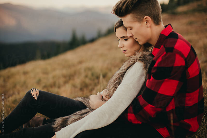 Young engaged couple explore mountain side at sunset by Luke Liable for Stocksy United