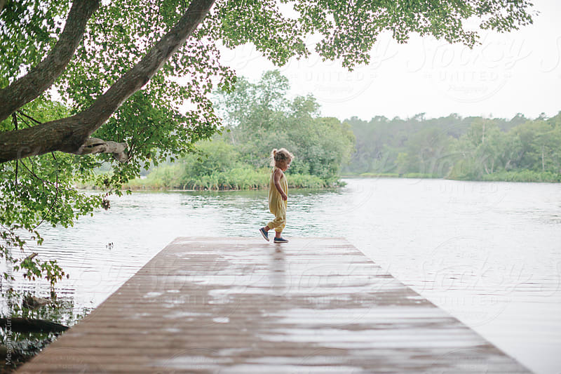 little girl exploring on a dock by Meaghan Curry for Stocksy United