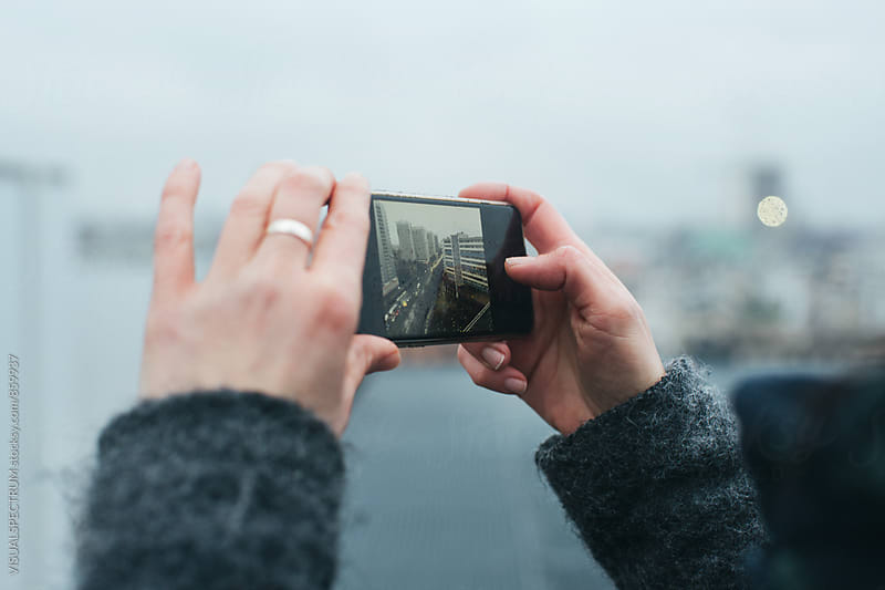 Close Up of Hands of Woman Taking Photo with Smartphone on Rainy Winter Day by VISUALSPECTRUM for Stocksy United