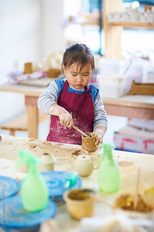 little asian girl learning pottery in studio by Bo Bo for Stocksy United