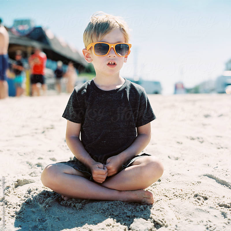 Boy sitting on the beach wearing sunglasses by Meghan Boyer for Stocksy United