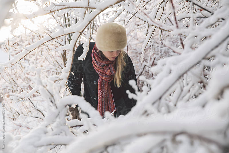 Woman pictured in snow landscape by Lior + Lone for Stocksy United