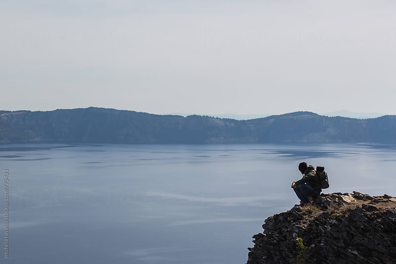Man sitting on the rock in front of the natural landscape  by michela ravasio for Stocksy United