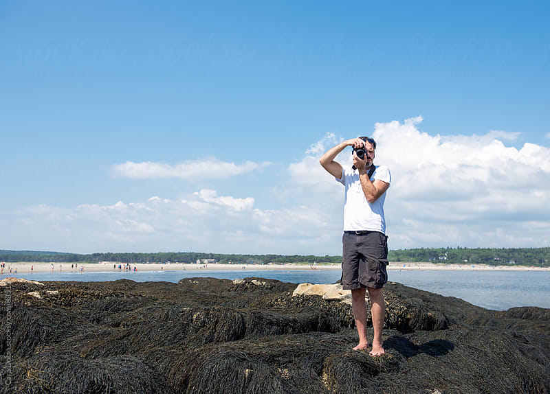 Man stands on seaweed at a beach taking a photo with a digital SLR camera by Cara Dolan for Stocksy United