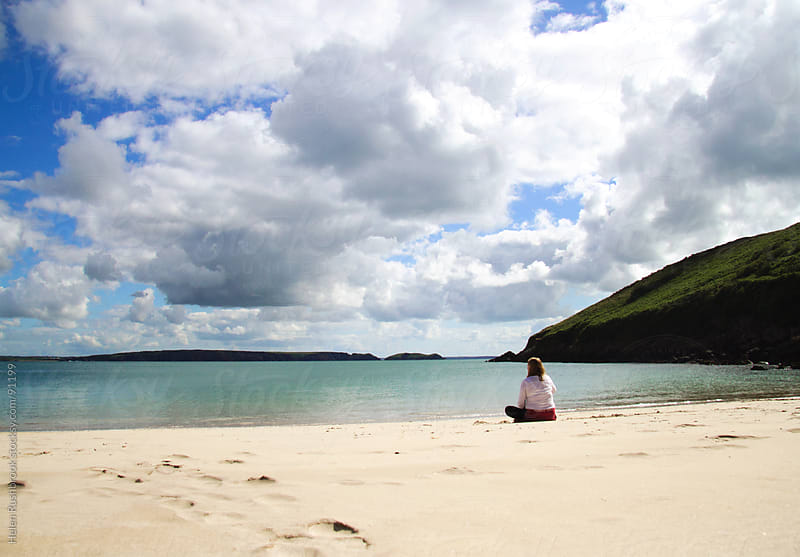 A woman sitting on a beautiful beach by Helen Rushbrook for Stocksy United