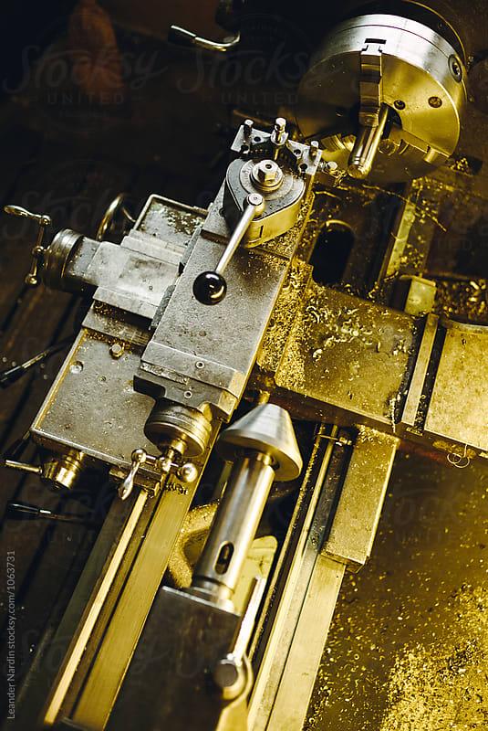 old vintage engine lathe shining in golden colors by Leander Nardin for Stocksy United