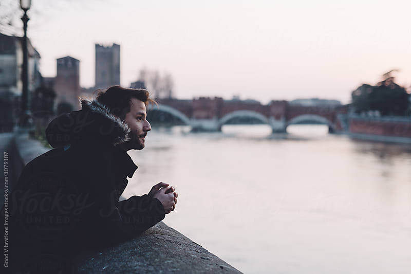 Man looking the river during a cold evening by Good Vibrations Images for Stocksy United