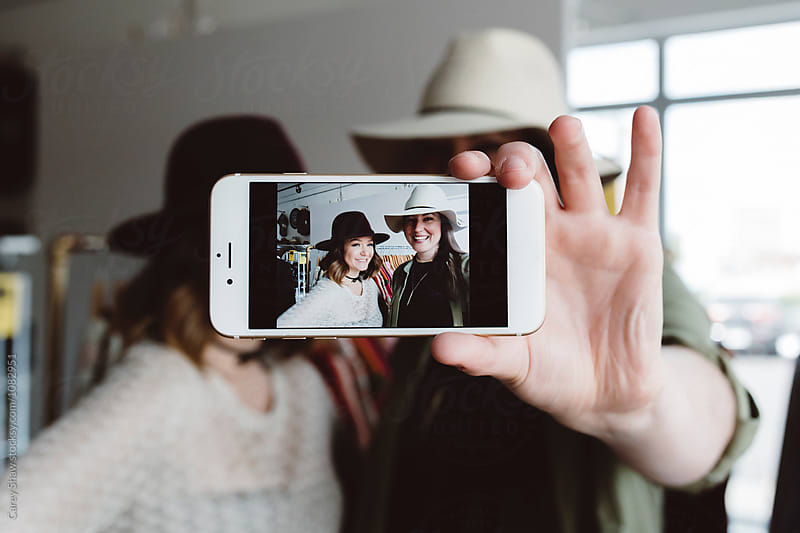 Friends taking selfie with cute hats by Carey Shaw for Stocksy United