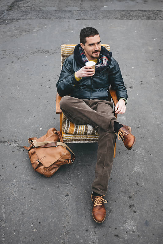 Man Sitting on an Armchair in a Flea Market by HEX. for Stocksy United