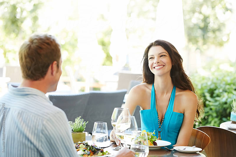 Beautiful couple eating at outdoor restaurant at luxury resort by Trinette Reed for Stocksy United