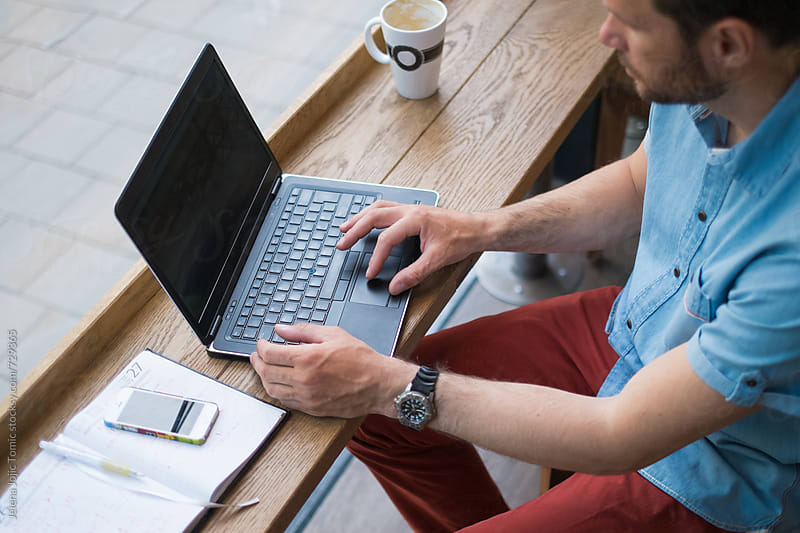 Man is working on a laptop at the caffee. by Jelena Jojic Tomic for Stocksy United