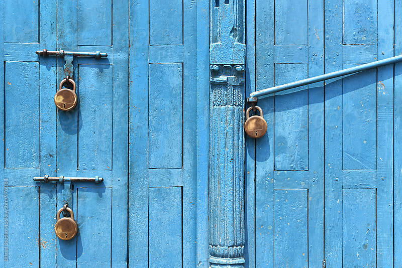 Three padlocks on a blue door by Bisual Studio for Stocksy United
