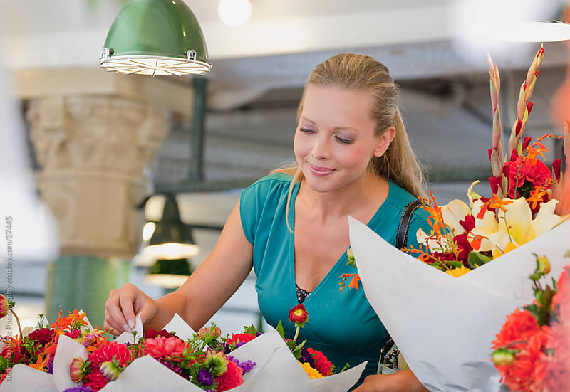 Smiling woman shopping for flowers by Andersen Ross Photography for Stocksy United