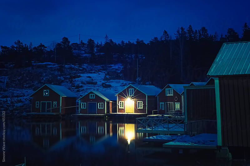 Fishing village on the sea at night - Sweden by Simone Becchetti for Stocksy United