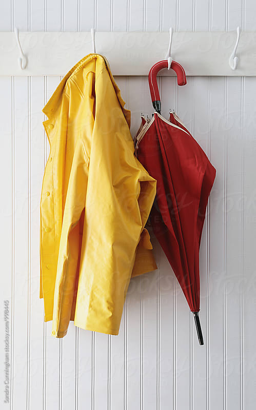 Yellow rain coat hanging with red umbrella by Sandra Cunningham for Stocksy United