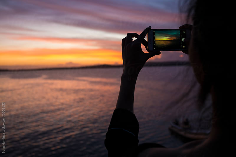 girl use cellphone take photo in sunset by Song Heming for Stocksy United