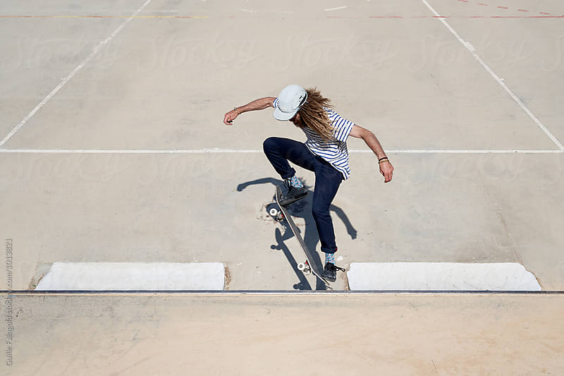 Skateboarder with long hair doing trick by Guille Faingold for Stocksy United