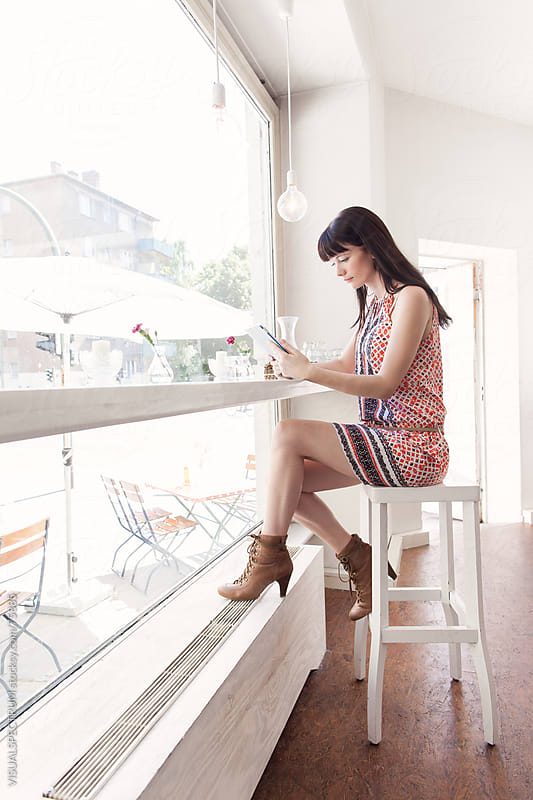 A Woman Reading on a Digital Tablet by VISUALSPECTRUM for Stocksy United