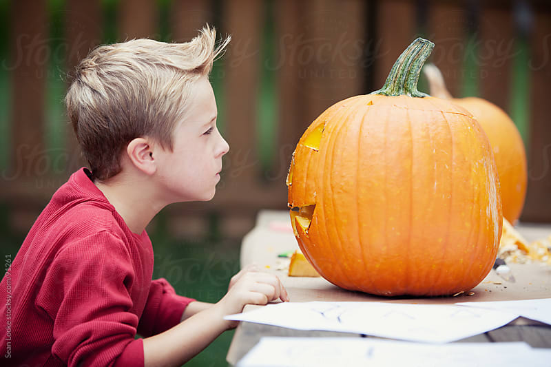 Pumpkins: Boy Staring Down His Jack-O-Lantern by Sean Locke for Stocksy United