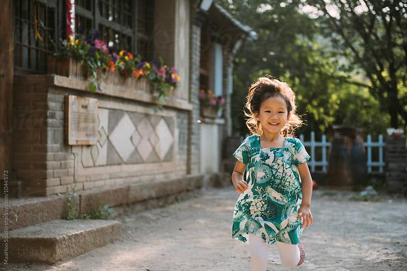 Adorable girl running in yard by Maa Hoo for Stocksy United