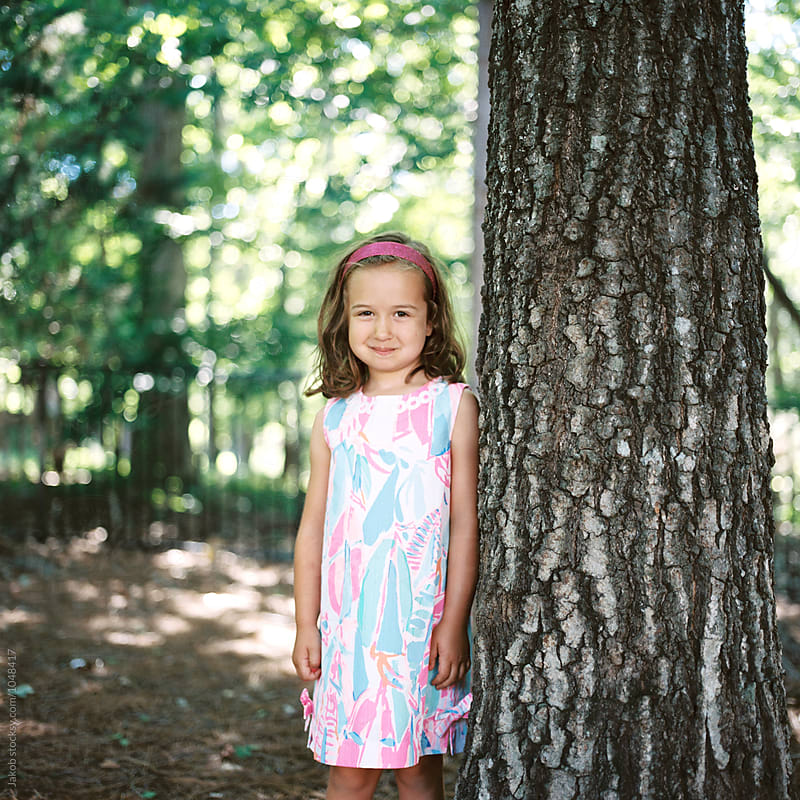 Beautiful young girl in a summer dress standing by a tree by Jakob for Stocksy United