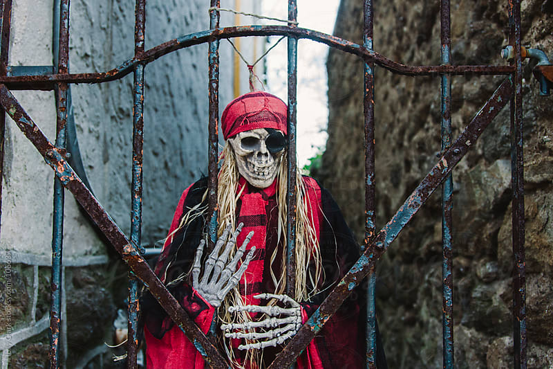 A skeleton decorates an iron gate to an alleyway. by Holly Clark for Stocksy United