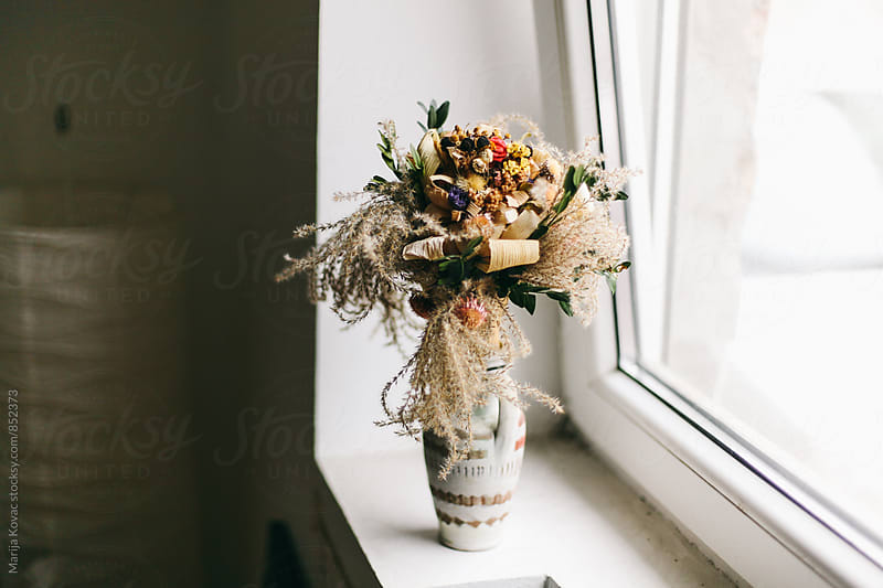 Colorful bouquet of flowers next to the window  by Marija Kovac for Stocksy United