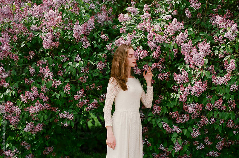 Beautiful woman breathing in perfume of lilac by Lyuba Burakova for Stocksy United