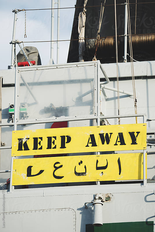 Keep away sign in english and arabian by Luca Pierro for Stocksy United