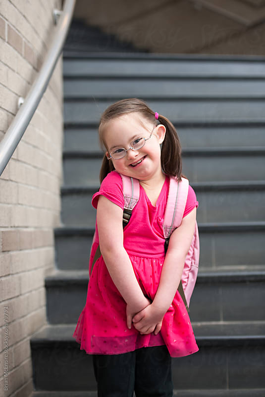 Exuberant Little Girl with Down Syndrome Smiling In School by Brian McEntire for Stocksy United