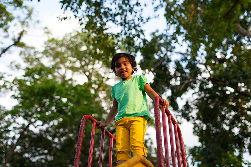 Little girl enjoying on the slide at a park by Saptak Ganguly for Stocksy United