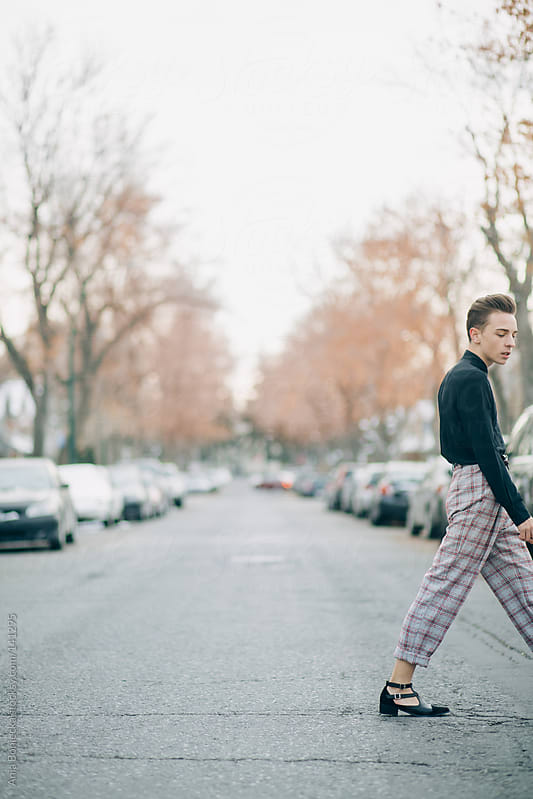 A dapper young man in plaid trousers  walking in the street by Ania Boniecka for Stocksy United