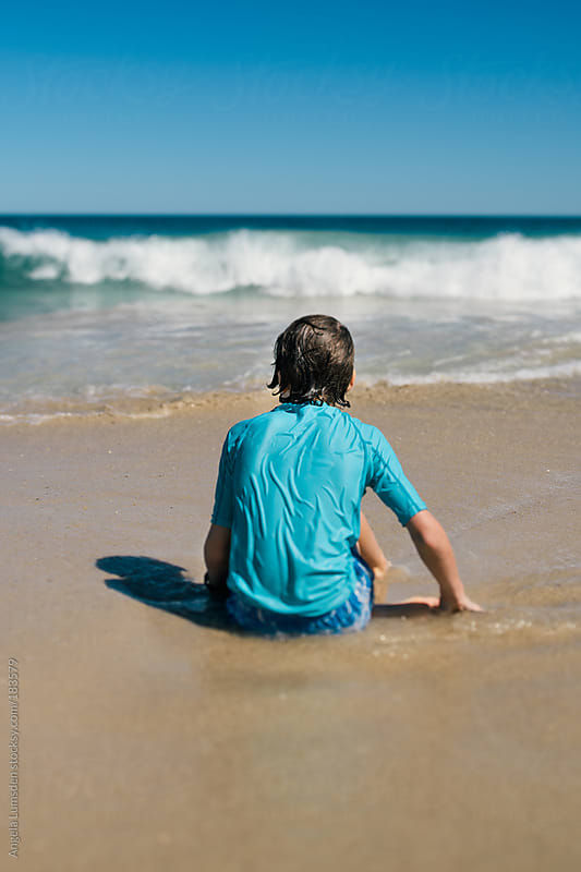 Child sitting on the beach watching the waves by Angela Lumsden for Stocksy United