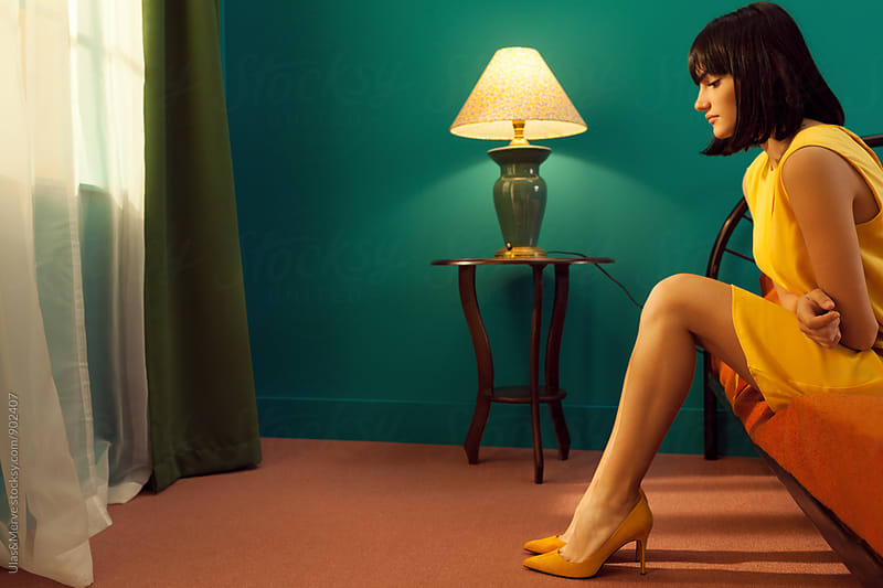 young elegant woman with yellow dress sitting on a bed in a retro room by Ulaş and Merve for Stocksy United